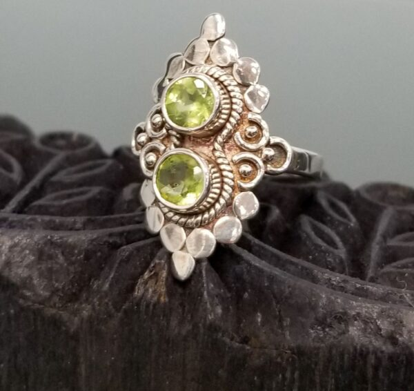 peridot and sterling silver ring on wood block