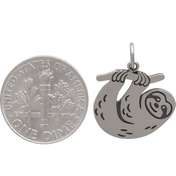 sloth pendant with dime to help show scale