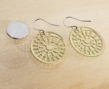 back of green spiral earrings with dime for scale