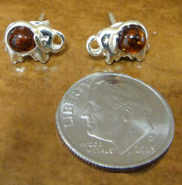 amber elephant next to dime for scale