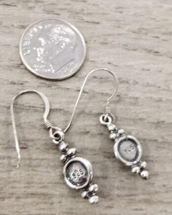back of stone inlay earrings with dime for scale