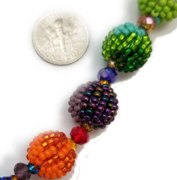 close up of beaded necklace with dime to help you gauge scale