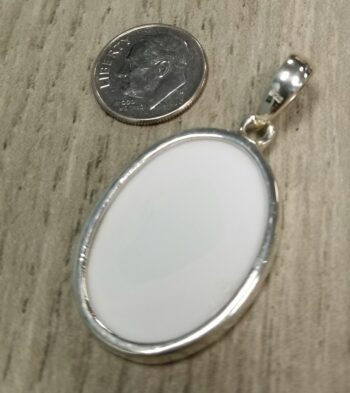 back of porcelain pendant with dime for scale