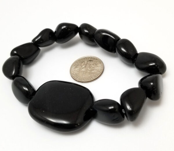 back of black agate bracelet with dime to help gauge scale