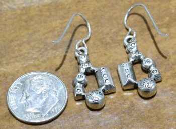 back of Gotham silver tone earrings by Patricia Locke with dime for size