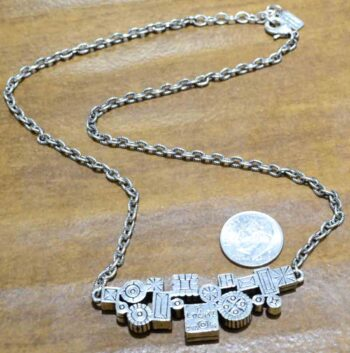 back of Madison Avenue necklace by Patricia Locke with dime for size