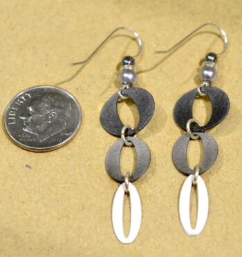 back of black, white, and gra ovals design drop earrings with dime