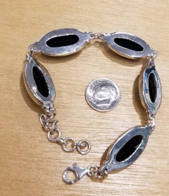 back of black onyx bracelet with dime for scale