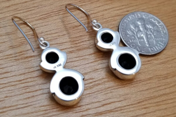 back of black onyx and sterling silver dangle earrings with dime for scale