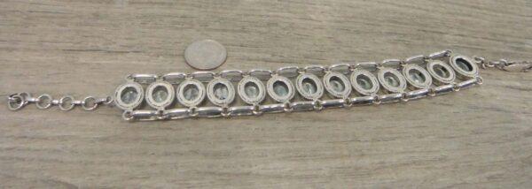 back of blue topaz bracelet with dime for size