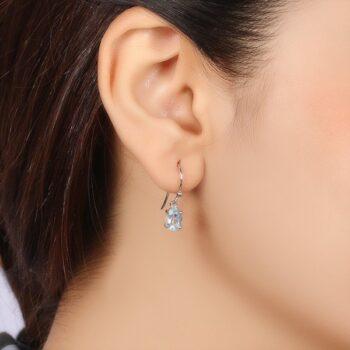 light blue topaz and sterling silver earrings on ear