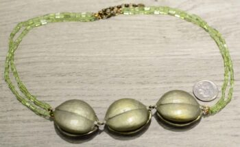 Back of Silver Seasons bonnet orchid necklace shown with dime for scale