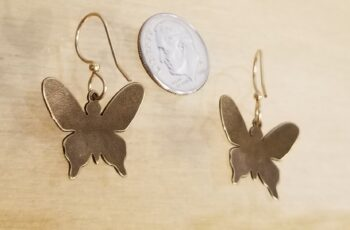 back of butterfly dangle earrings with dime for scale