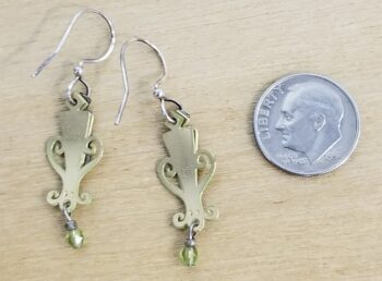 Back of green earrings with dime for scale