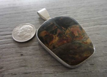 Handmade butterfly wing jasper and sterling silver pendant shown with dime (not included) for scale