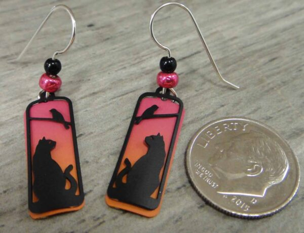 These cat and bird silhouette earrings are handmade by Sienna Sky pictured with dime for scale