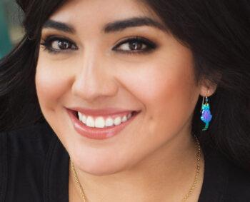 Holly Yashi cat dangle earrings on woman