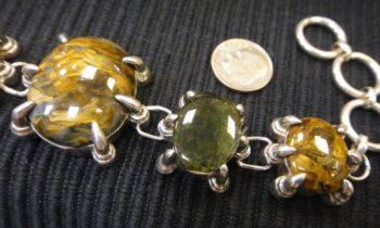 close-up of pietersite and moldavite stone bracelet with dime