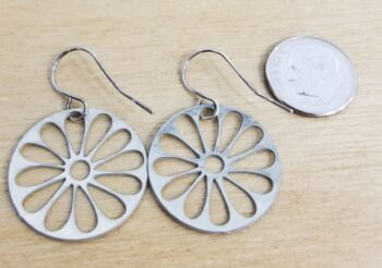 back side of silver-tone daisy earrings with dime for scale