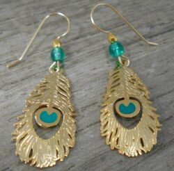 These gold and green colored peacock feather earrings are handmade by Sienna Sky.