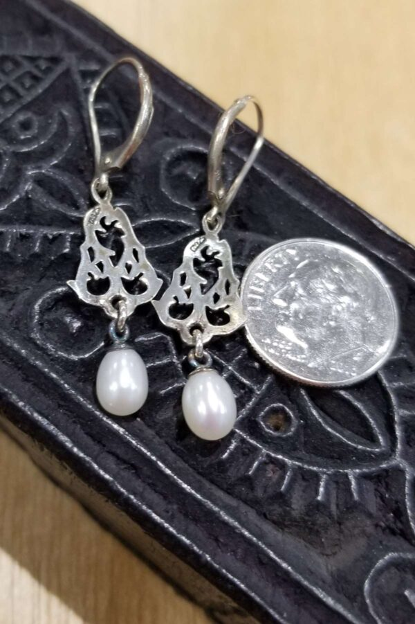 back of fresh water pearl earrings with dime for scale