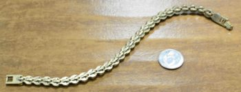 back of Game, Set, Match gold tone bracelet by Patricia Locke with dime for size