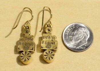 back of Girlfriends two tone earrings by Patricia Locke with dime for size