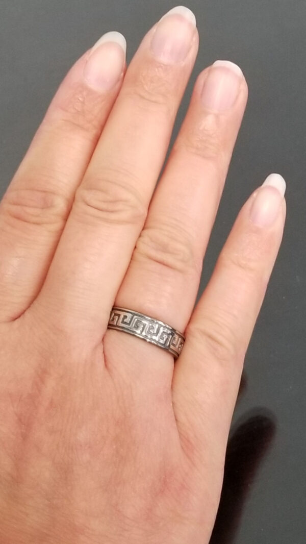 Greek key pattern etched sterling silver ring on hand