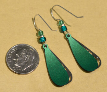 back of green and teal silvertone swirl Adajio earrings with dime