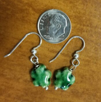 back of green ceramic daisy earrings with dime for scale