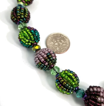 purple and green necklace close up with dime to help gauge scale