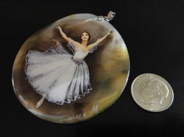 This hand painted mother of pearl shell pendant is shown here with a dime for scale.