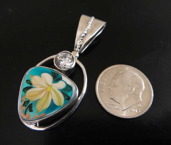 THis hand painted mother of pearl pendant was designed by Anna King (shown with dime for scale).