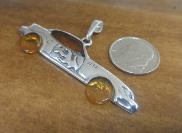 """This honey brown amber and sterling silver pendant features a """"hot rod"""" car."""