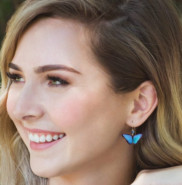 Blue butterfly earrings on model