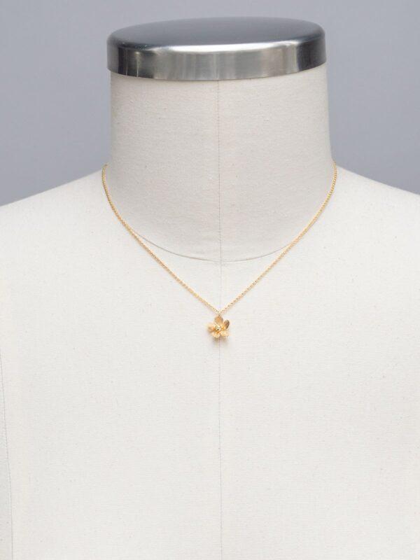 goldtone plumeria flower necklace on mannequin