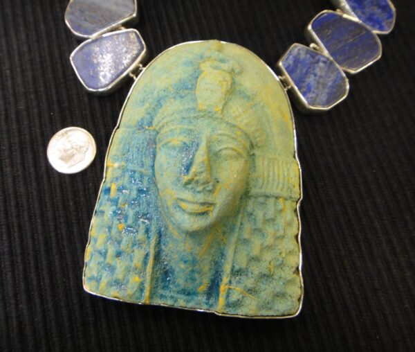 close-up of King Tut bust on lapis lazuli necklace with dime for size