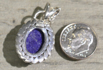 back of handmade lapis lazuli oval pendant with silver detail and dime for scale