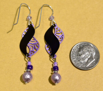 back of purple and black swirl beaded earrings with dime