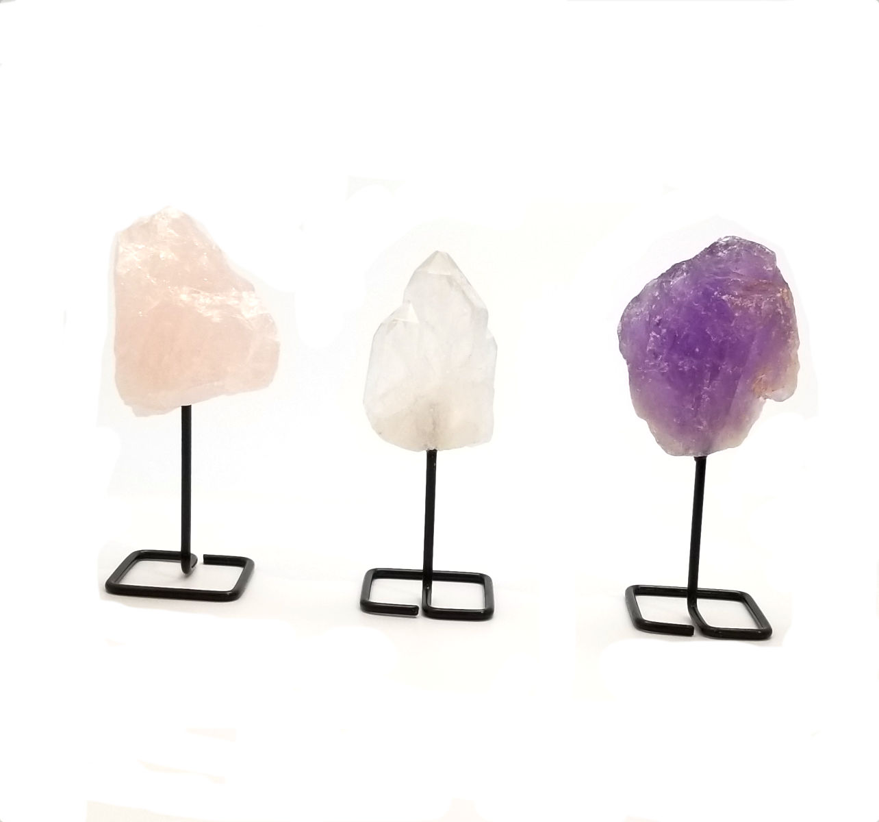 Rose quartz, clear quartz, and amethyst crystals on stands