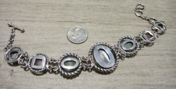 back of blue and green kyanite, agate, and zebra jade sterling silver bracelet with dime for scale