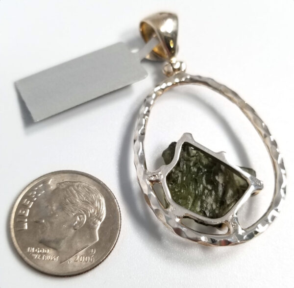 Back of moldavite pendant with dime for scale