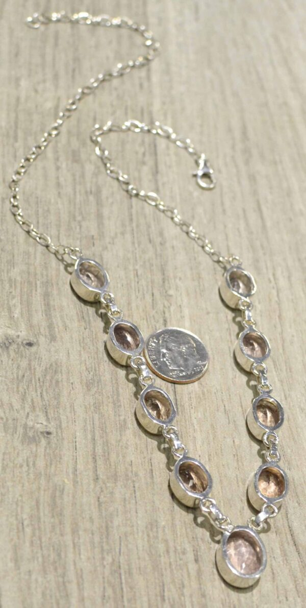 back of morganite necklace with dime for scale