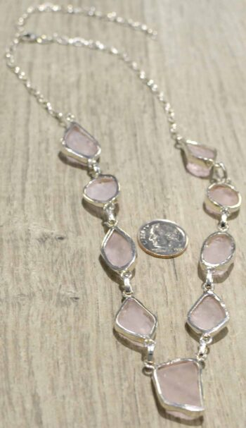 back of handmade rough morganite necklace with dime for size