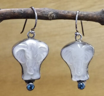 Elephant earrings carved from white mother of pearl shell with blue topaz gemstone accents