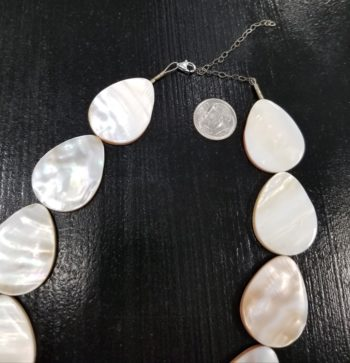 close-up of clasp on long mother of pearl shell necklace with dime for scale