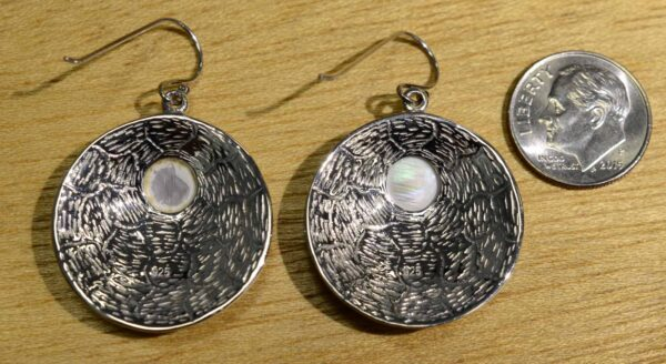 back of mother of pearl mosaic earrings with dime for size