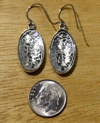 back of enamel and mother of pearl earrings with dime for size