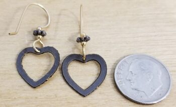 back of Joseph Brinton heart earrings with dime for scale