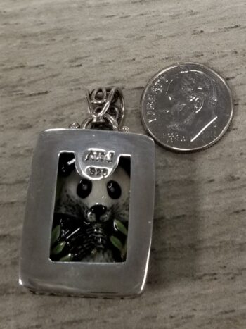 back of panda pendant with dime for scale
